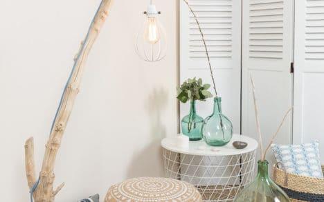 Lampadaire en bois flotté, l'abat-jour est une cage goutte en métal couleur blanc, la douille E27 est en bakélite lisse blanche, le câble électrique est rond en coton bleu et lin naturel, le socle est en acier peint en noir avec une feutrine collée en dessous.