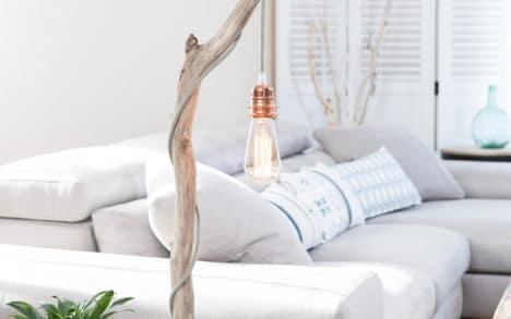 Lampe en bois flotté, la douille 2 bagues E27 est en métal couleur cuivre, le câble électrique est en coton vert thym et lin naturel, l'ampoule Edison est à filament de carbone, le socle est en acier peint en noir avec une feutrine collée en dessous.