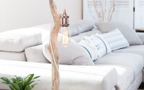 Lampe en bois flotté, la douille E27 est en aluminium finition cuivrée, le câble électrique est en lin naturel, l'ampoule Edison est à filament de carbone, le socle est en acier peint en noir avec une feutrine collée en dessous.